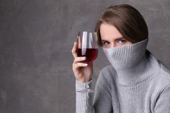 Girl with wine hiding her face by collar. Close up. Gray background Stock Photos