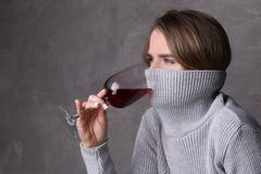 Lady drinking wine with collar on her face. Close up. Gray background Stock Photos