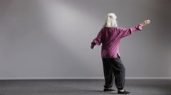 A senior aged woman doing Tai Chi, wide shot Stock Footage