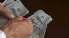Close-up of a businessman hands counting hundred dollar bills at table Stock Footage