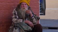 A homeless man sits on the street. Stock Footage