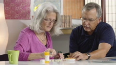 Senior couple counting out pills Stock Footage