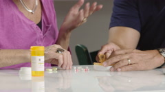 Senior man and woman counting pills, close up Arkistovideo