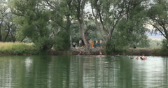 Teenage fun local swimming pond rope swing DCI 4K Stock Footage