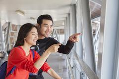 Couples of younger asian traveling man and woman looking and pointing to tour Stock Photos