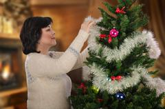 Woman makes Christmas tree more attractive by adding tinsels Stock Photos