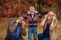 Young smiling family with closed eyes by leaves in outdoors Stock Photos