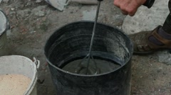 Mixing cement in a bucket Stock Footage