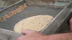 Sifting sand through a sieve Stock Footage