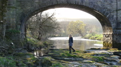 Pretty young woman walking on rocks next to an aqueduct and river. Stock Footage