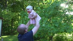 Young daddy lift his happy baby daughter near tulip tree in park. 4K Stock Footage