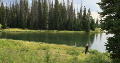 Woman fishing shore of mountain forest lake DCI 4K Stock Footage