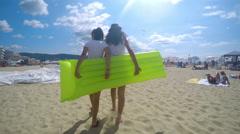 Two girls with inflatable air bed walk on sandy beach, trekking 4k shot Stock Footage