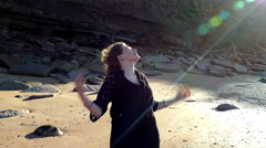 Pretty girl standing smiling in a rocky cove in strong sunshine. Stock Footage
