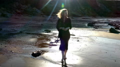 Pretty young woman walking on sand towards camera in backlit sunshine. Stock Footage