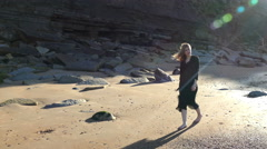 Pretty young woman walking on sand in bright sunshine, in a secluded cove. Stock Footage