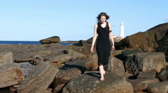 Pretty young woman on rocks by sea, with lighthouse in background. Stock Footage