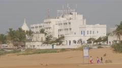 Tourists walking on beach with big white resort,Puri,India Stock Footage