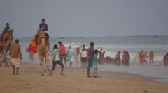 Camel and drivers on beach with tourists,Puri,India Stock Footage