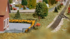 Model cargo trains and tram passing by, meet and cross on a diorama Stock Footage