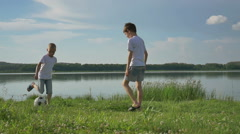 Father and two son playing football on the beach at the day time. Concept of Stock Footage