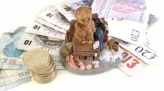 Sterling (pounds) and teddy bear ornament. Stock Footage