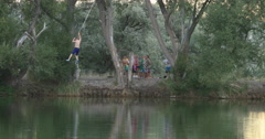 Friends rope swing summer pond DCI 4K Stock Footage