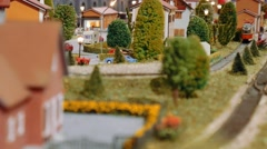 Model trains transit and a tram departs on a diorama Stock Footage