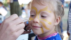 Painting body art on a face of little cute child girl - happy childhood portrait Stock Footage