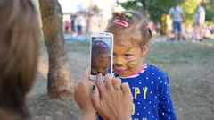 Painting body art on face of little cute child girl - mom takes photo picture Stock Footage