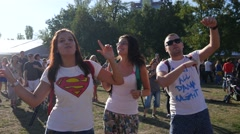 Young people fans cheerfully dance raise wave hands in air during open air fest Stock Footage