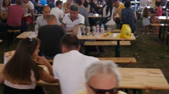 People crowd eating during food festival sit at tables under a big awning tent Stock Footage