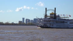 A paddlewheel steamboat passes on the Mississippi River with new Orleans in the Stock Footage