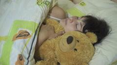 Young woman, girl sleeping in bed hugging teddy bear . Stock Footage