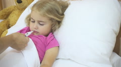 Sick little girl having her temperature taken with a digital thermometer. Chi Stock Footage