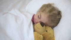 Child little girl sleeping in bed hugging teddy bear . Stock Footage