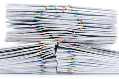 Colorful heart-shaped paperclip on top of pile overload paperwork Stock Photos
