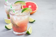 Cold pink cocktail with fresh grapefruit, lime, copy space Stock Photos