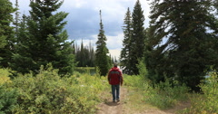 Man hikes trail mountain valley lake DCI 4K Stock Footage