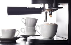 Espresso pouring from coffee machine. Stock Photos