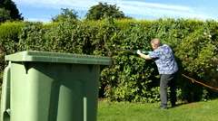 Dolly shot of man trimming a garden hedge in front of a wheely bin. Stock Footage
