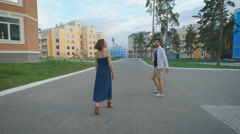 Man and woman strolling along the fashionable residential area Stock Footage