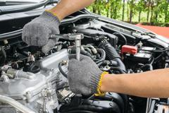 Hands of car mechanic in auto repair service. Stock Photos