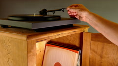 Hand placing stylus on long playing record (LP) on turntable. Stock Footage