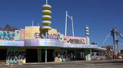 An abandoned and graffiti covered game arcade at an amusement park presents a Stock Footage