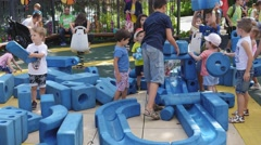 Kids play on colorful outdoors playground for children - active happy childhood Stock Footage