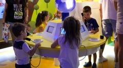 Kids enjoy listen to educational phone sound stand in cognitive children museum Stock Footage