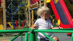 Young father rolls his son on the carousel at the playground Stock Footage