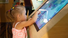 Cute little child girl type an educational multimedia cognitive gaming display Stock Footage