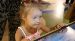 Cute little child girl type an educational multimedia gaming display Stock Footage
